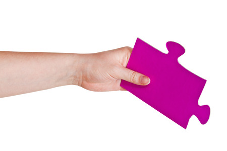 female hand holding big pink paper puzzle piece isolated on white background photo