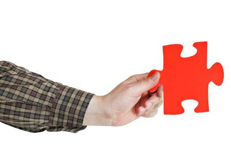 male hand holding big red paper puzzle piece isolated on white background photo