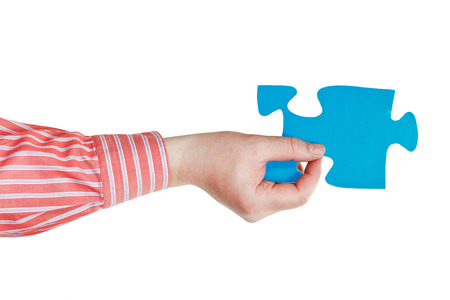 male hand holding big blue paper puzzle piece isolated on white background photo