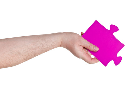 male hand holding big pink paper puzzle piece isolated on white background photo
