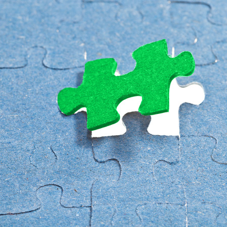 setting the last green piece of puzzle in free space in assembled jigsaw puzzles photo