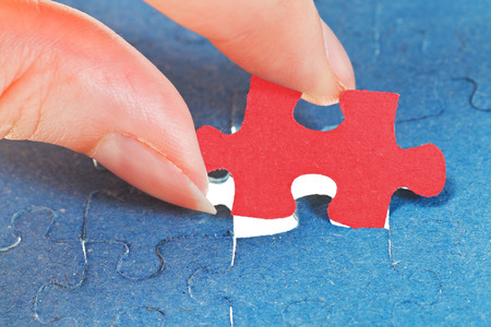 attaching: attaching the last red piece of puzzle in free space in assembled jigsaw puzzles