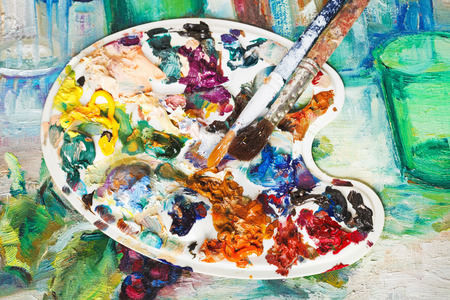 pallette: used artistic pallette with oil paints and paintbrushes on picture canvas