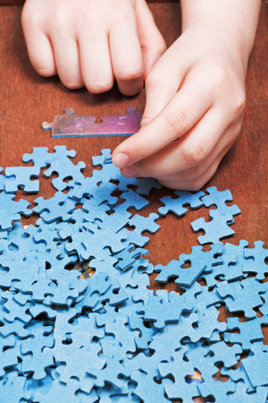assembling of jigsaw puzzles on wooden table photo
