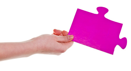 female hand holding big pink paper puzzle piece isolated on white  photo