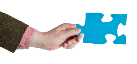 male hand holding big blue paper puzzle piece isolated on white  photo