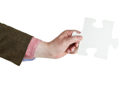 male hand holding big white paper puzzle piece isolated on white  photo