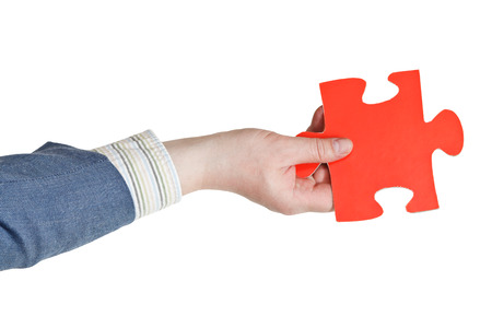 male hand holding big red paper puzzle piece isolated on white  photo