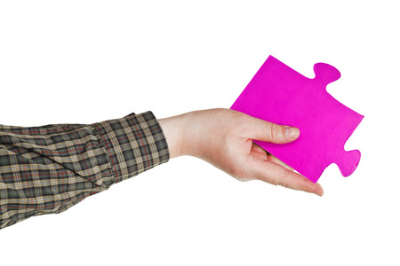 male hand holding big pink paper puzzle piece isolated on white  photo