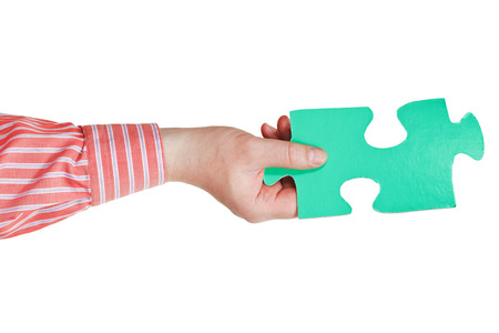 male hand holding big green paper puzzle piece isolated on white  photo
