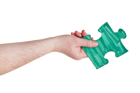 male hand with painted green puzzle piece isolated on white  photo