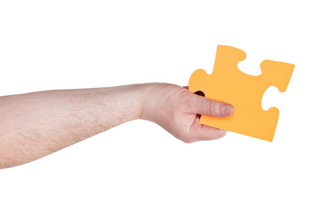 male hand holding big yellow paper puzzle piece isolated on white  photo