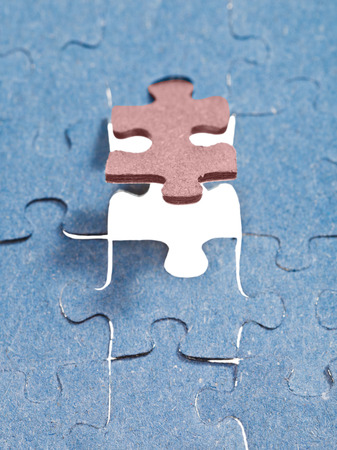 setting the last brown piece of puzzle in free space in assembled jigsaw puzzles photo