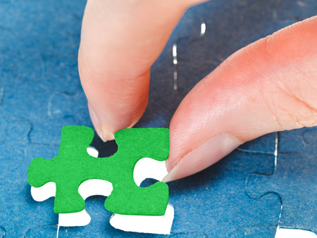 fitting the last green piece of puzzle in free space in assembled jigsaw puzzles photo