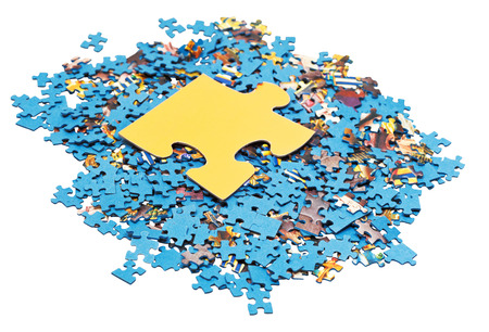 big puzzle piece on pile of disassembled blue jigsaw puzzles isolated on white background photo