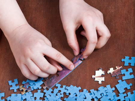 linking of jigsaw puzzles on wooden table photo
