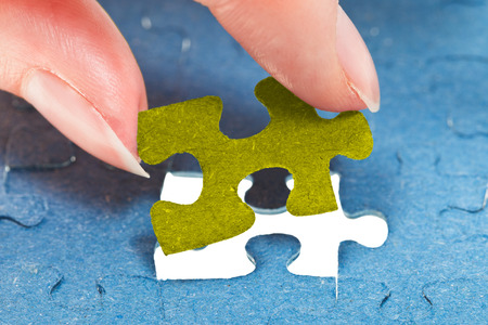 inserting the last piece of puzzle in free space in assembled jigsaw puzzles photo