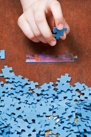 choosing of jigsaw puzzles on wooden table photo