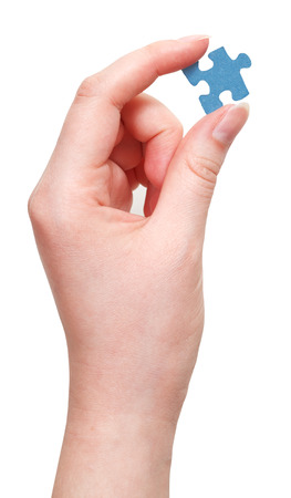 female hand holding blue puzzle piece isolated on white background photo