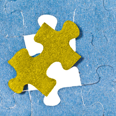 setting the last yellow piece of puzzle in free space in assembled jigsaw puzzles photo