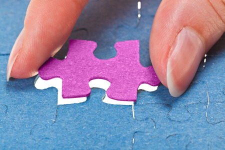 inserting the last pink piece of puzzle in free space in assembled jigsaw puzzles photo