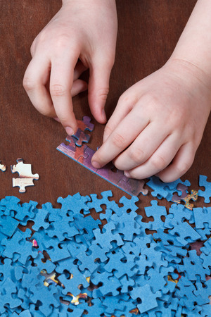 connecting of jigsaw puzzles on wooden table photo