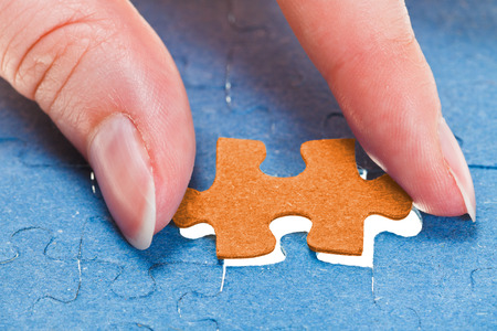inserting the last orange piece of puzzle in free space in assembled jigsaw puzzles photo