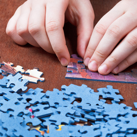 playing with jigsaw puzzles on wooden table photo
