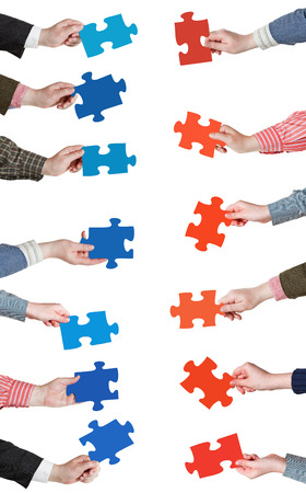 set of red and blue puzzle pieces in opposite sides in people hands isolated on white background photo