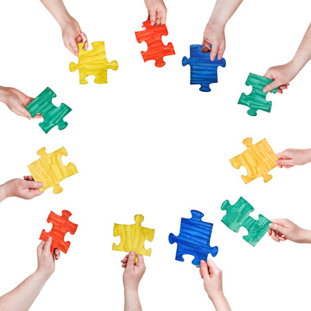 set of painted puzzle pieces in people hands in circle isolated on white background photo