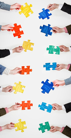set painted puzzle pieces in people hands on grey background photo