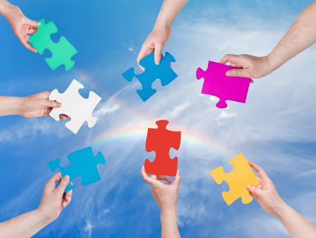 circle of people hands with different puzzle pieces with blue sky and rainbow background photo