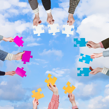 circle of people hands with different puzzle pieces with light blue sky and white clouds background photo