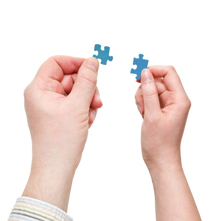 male and female two hands holding little puzzle pieces isolated on white background photo