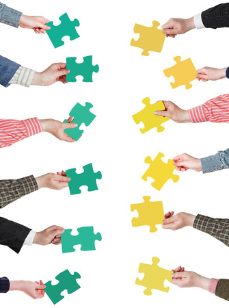 set of green and yellow puzzle pieces in opposite sides in people hands isolated on white background photo