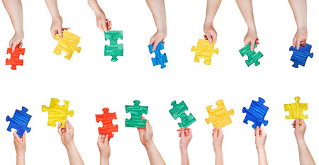 set of painted puzzle pieces in people hands isolated on white background photo