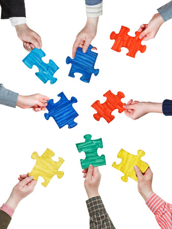 set of different puzzle pieces in people hands in circle isolated on white background photo