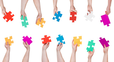 set of color puzzle pieces in people hands isolated on white background photo