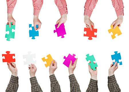 male hands in shirt sleeves with different puzzle pieces isolated on white background photo
