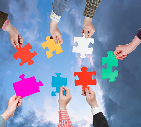 circle of people hands with different puzzle pieces with dark grey evening sky background photo