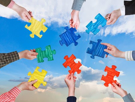 circle of people hands with different puzzle pieces with afternoon blue sky background photo