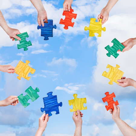 circle of people hands with painted puzzle pieces with blue sky and white clouds background photo