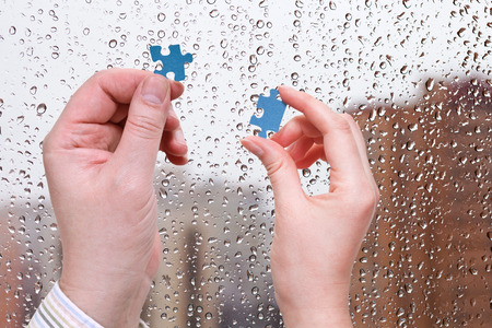 male and female hands with little puzzle pieces with home window and rain drops background photo