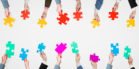 set different puzzle pieces in people hands on grey background photo