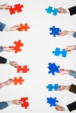 set of red and blue puzzle pieces in opposite sides in people hands on grey background photo