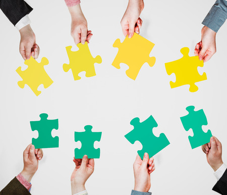 set of green and yellow puzzle pieces in opposite sides in people hands on grey background photo