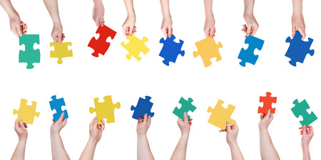 set different puzzle pieces in people hands isolated on white background photo