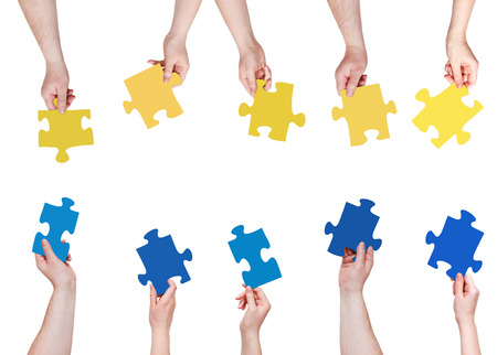 set of blue and yellow puzzle pieces in opposite sides in people hands isolated on white background photo