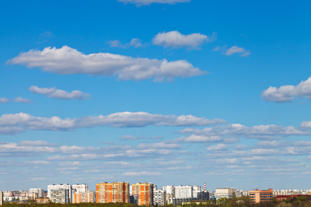 stratus: white clouds in blue sky over urban district in spring