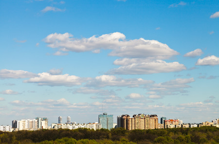 blue spring sky with white clouds over urban residential district photo